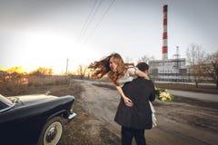 Schöne Hochzeitspaare in der Landschaft nahe bei dem Retro- Auto Mannbräutigam nimmt, Braut in seinen Armen halten lächelnder glü Stockfotografie