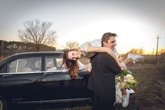 Schöne Hochzeitspaare in der Landschaft nahe bei dem Retro- Auto Mannbräutigam nimmt, Braut in seinen Armen halten lächelnder glü Lizenzfreies Stockfoto