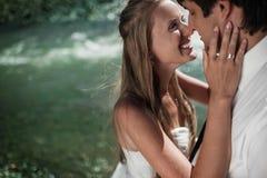 Schöne Hochzeitspaare, die auf dem Fluss lächeln lizenzfreie stockfotos