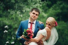 Schöne Hochzeitspaare im Park Küssen Sie und umarmen Sie sich Lizenzfreie Stockbilder