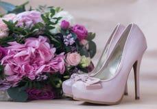 Schöne Hochzeitsschuhe mit hohen Absätzen und ein Blumenstrauß von bunten Blumen Stockfotografie