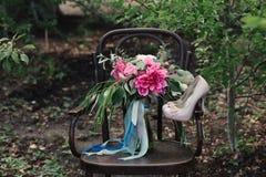 Schöne Hochzeitsschuhe mit hohen Absätzen und ein Blumenstrauß von bunten Blumen auf einem Weinlesestuhl auf der Natur Lizenzfreies Stockbild