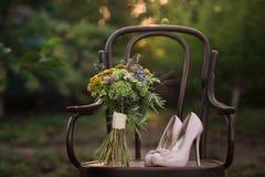 Schöne Hochzeitsschuhe mit hohen Absätzen und ein Blumenstrauß von bunten Blumen auf einem Weinlesestuhl auf der Natur im Sonnenu Stockfotografie
