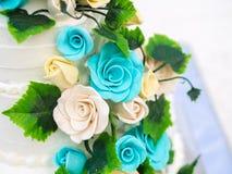 Schöne Hochzeitstorte mit den blauen und gelben Rosen Stockfotos