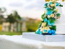 Schöne Hochzeitstorte mit den blauen und gelben Rosen Lizenzfreies Stockfoto