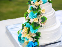 Schöne Hochzeitstorte mit den blauen und gelben Rosen Lizenzfreies Stockbild