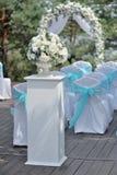 Schöne Hochzeitszeremonie verziert mit Bogen, Blumen und Stühlen Stockfoto