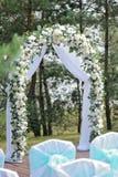 Schöne Hochzeitszeremonie verziert mit Bogen, Blumen und Stühlen Stockfotos