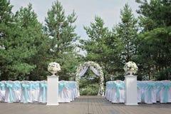 Schöne Hochzeitszeremonie verziert mit Bogen, Blumen und Stühlen Stockfotografie