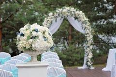 Schöne Hochzeitszeremonie verziert mit Bogen, Blumen und Stühlen Lizenzfreie Stockfotografie
