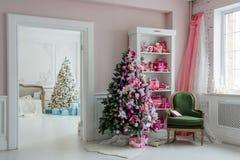 Schöne holdiay verzierte Räume mit Weihnachtsbäumen, Regal und rosa blauen Geschenken auf ihm, grüner Stuhlausgangsinnenraum Stockfoto