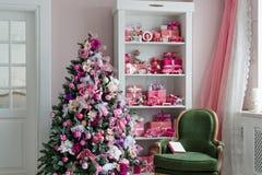 Schöne holdiay verzierte Räume mit Weihnachtsbäumen, Regal und rosa blauen Geschenken auf ihm, grüner Stuhlausgangsinnenraum Stockfotos