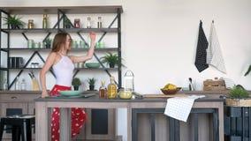 Schöne Ingwerfrau, die sexy Bewegungen in der modernen Küchen-, glücklicher und froherjungen Frau hat Spaß im Haus tanzt stock footage