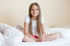 Schöne 10 Jahre alte Mädchen mit dem langen Haar, das auf Bett sitzt Lizenzfreie Stockfotografie
