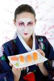 Schöne Japan-Geishafrau mit Sushi Lizenzfreie Stockfotos