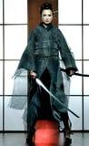 Schöne japanische Kimonofrau mit Samuraiklinge Lizenzfreie Stockfotografie