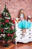 Schöne Jugendblondine sitzen auf einem weißen nightstand nahe Weihnachtsbaum, mit vielen Spielwaren und Geschenken Stockfotografie