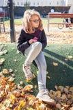 Schöne Jugendliche in den Gläsern, die im Park sitzen Stockfotografie