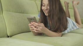 Schöne Jugendliche, die den Spaß in Verbindung steht auf Smartphonevorrat-Gesamtlängenvideo hat stock footage