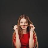 Schöne Jugendliche, die lustige Gesichter unter Verwendung ihrer langen Blondine macht Stockbild