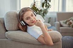 Schöne Jugendliche mit hörender Musik des Smartphone und der Kopfhörer stockbild