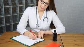 Schöne junge Ärztin, die vor der Funktionstabelle hält Glas Tabletten und an schreibt Verordnung sitzt stock video footage