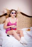 Schöne Junge überraschten blonde Frau in den rosa Farbpyjamas, die aufpassenden Film in den Gläsern 3D sitzen und Popcorn essen Lizenzfreie Stockbilder
