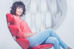 Schöne junge überzeugte Frau, die im roten Stuhl gegen weiße Wand sitzt Stockfotografie