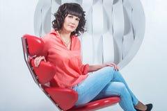 Schöne junge überzeugte Frau, die im roten Stuhl gegen weiße Wand sitzt Lizenzfreie Stockfotografie