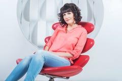 Schöne junge überzeugte Frau, die im roten Stuhl gegen weiße Wand sitzt Stockfoto