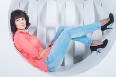Schöne junge überzeugte Frauenlüge im Kreis auf Hintergrundweißwand Stockbilder