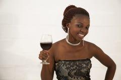 Schöne junge afrikanische Frau, die ein Glas Rotwein hält Stockfotos