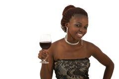 Schöne junge afrikanische Frau, die ein Glas Rotwein hält Stockbild