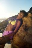 Schöne junge afrikanische Frau, die im Bikini am Strand aufwirft Stockfotografie