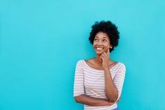 Schöne junge afrikanische lächelnde und denkende Frau lizenzfreie stockfotos