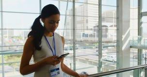 Schöne junge Afroamerikanergeschäftsfrau, die an Handy im Büro 4k arbeitet stock footage