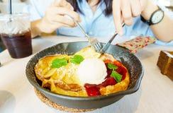 Schöne junge Asiatin genießen, selbst gemachte Fruchtpfannkuchen mit Banane, Erdbeere, Eiscreme und gefrorenem Kaffee zu essen Kö lizenzfreies stockbild