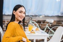 schöne junge asiatische Frau, die an der Kamera beim Sitzen lächelt lizenzfreies stockfoto