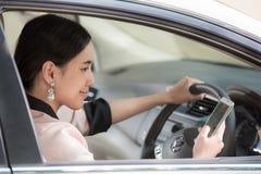 Schöne junge asiatische Frau, die Karte im Mobile in einem Auto verwendet Lizenzfreies Stockbild