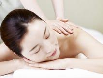 Schöne junge asiatische Frau, die Massage im Badekurortsalon empfängt lizenzfreies stockbild