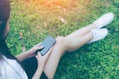 Schöne junge asiatische Frau, die Smartphone im Garten verwendet Stockbild