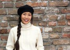 Schöne junge asiatische Frau mit Hut draußen lächelnd Stockfotografie