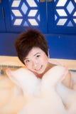 Schöne junge asiatische Frau nimmt Schaumbad Stockbild