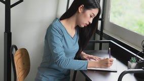 Schöne junge asiatische Frauenhandschrift auf Notizbuch auf Tabelle, Mädchenarbeit mit Buch oder Tagebuch zu Hause stock video