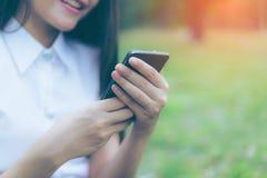 Schöne junge asiatische lächelnde Frau beim Ablesen ihres Smartphone Stockfotos