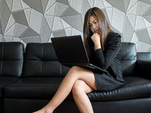 Schöne junge Asien-Geschäftsfrau, die auf dem Sofa, arbeitend mit Laptop-Computer und des Abnutzungsschwarzanzugs aufpassendem Mo lizenzfreie stockfotos