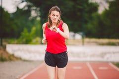 Schöne junge Athlet Caucasian-Frau mit der großen Brust im roten T-Shirt und in den kurzen kurzen Hosen Rütteln, laufend in das S lizenzfreies stockfoto