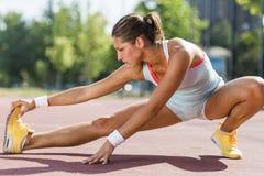 Schöne junge athletische Frau, die in Sommer ausdehnt Stockbild