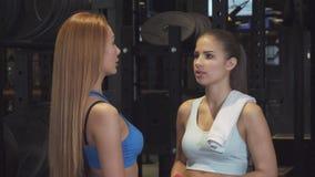 Schöne junge athletische Frauen, die zur Kamera aufwirft an der Turnhalle lächeln stock video