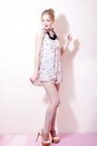 Schöne junge attraktive blonde Frau des Pinupmädchens in einem Kleid und in den Schuhen der hohen Absätze Stockfotografie